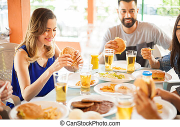 Cute woman eating a hamburger with friends