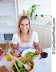 Cute woman eating a salad in the kitchen