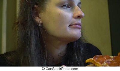 Cute woman enjoying pizza sitting in cafe.