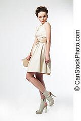 Cute woman fashion model in retro dress posing