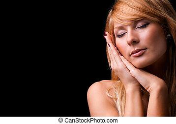 Cute woman gesturing a sleep isolated against on a black...