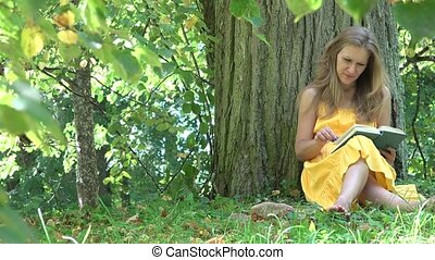 Cute woman girl in yellow dress sit under old tree enjoy...