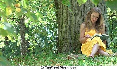 Cute woman girl in yellow dress sit under old tree enjoy...