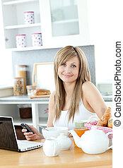 Cute woman having breakfast in the kitchen