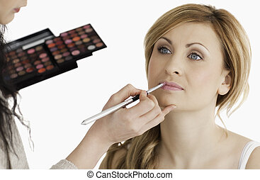 Cute woman having her make up done by a make up artist