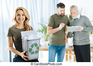 Cute woman holding a bin with recyclable paper and smiling