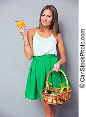 Cute woman holding basket with vegetables - Portrait of a ...