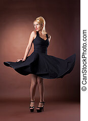 Cute woman in black pinup style dance on dark background