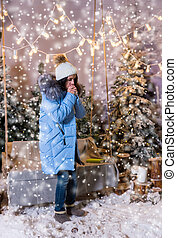 Cute woman in blue down jacket warming hands and standing near swing with a blanket under the flashlights in a snow-covered park