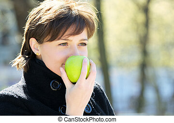 Cute woman in park with apple