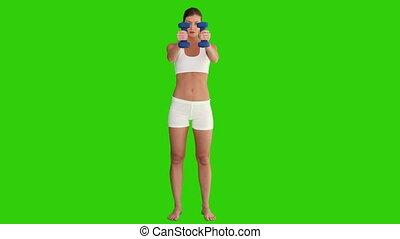 Cute woman in sporstwear with dumbbells