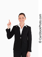 Cute woman in suit pointing at a copy space
