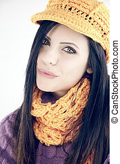 Cute woman in winter with hat and scarf looking camera