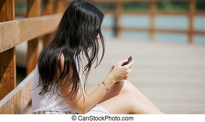 Cute woman is reading text message on mobile phone while sitting in the park.