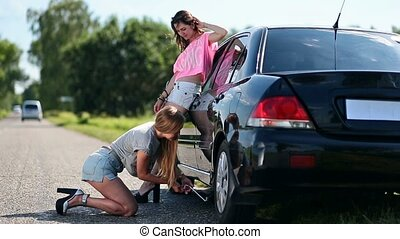 Pretty woman on high heels and shorts is kneeling and jacking up her car to change flat tire with spare one. Her girlfriend is standing near car giving her advice on how to use screw-jack.