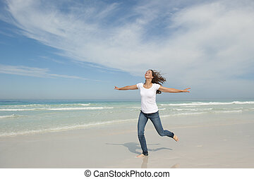 Cute woman joyful running at beach