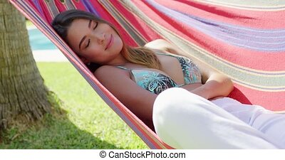 Cute woman laying back in hammock - Single cute woman with...