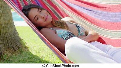 Cute woman laying back in hammock