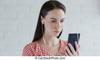 Cute woman listening to music and using smartphone