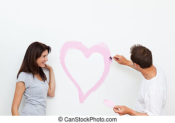 Cute woman looking at her boyfriend painting a heart