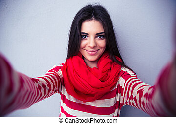 Cute woman making selfie over gray background - Happy cute...