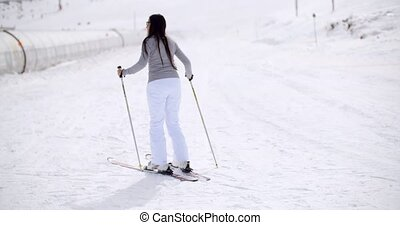 Cute woman on skis at bottom of hill