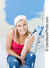 Cute woman  painting a room in her