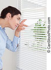 Cute woman peeking out a window