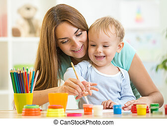 Cute woman playing and painting with child