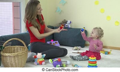 Cute woman playing with her baby in while sitting on a carpet in living room.