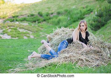 Cute woman posing sitting on the hay.