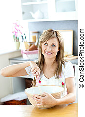 Cute woman preparing a cake in the kitchen