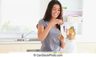 Cute woman preparing a smoothie with her blender