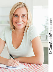 Cute woman proof-reading a text smiles into camera in the ...