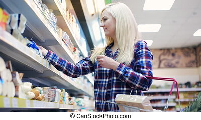 cute woman pushing shopping with basket in supermarket -...