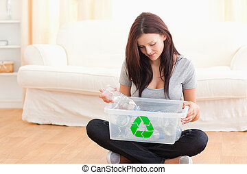Cute woman putting bottles in a recycling box