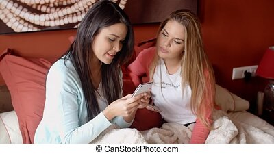 Cute woman showing friend her phone - Cute young woman with...