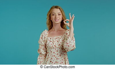 Cute woman showing okay sign over blue background. Positive ...