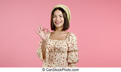 Cute woman showing okay sign over pink background. Positive ...