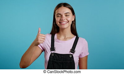 Cute woman showing thumb up sign over blue background. ...