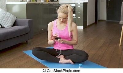 Cute woman sitting on yoga mat and browsing mobile phone for...