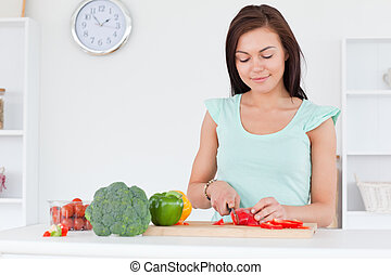 Cute woman slicing a pepper
