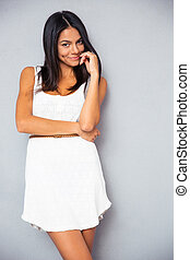 Cute woman standing in trendy white dress