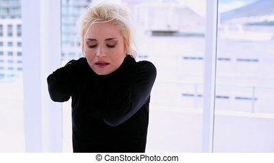 Cute woman suffering from neck pain standing in bright room