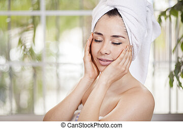 Cute woman taking care of her skin