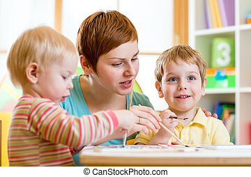 cute woman teaching kids to paint at nursery or playschool