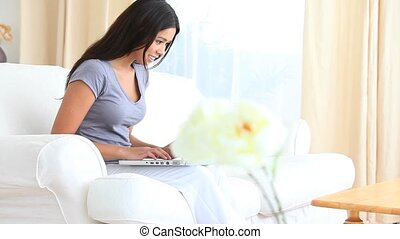 Cute woman typing on her laptop