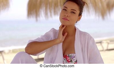 Cute woman under shade umbrella at beach - Single cute young...