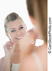 Cute woman using dental floss in front of mirror