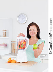 Cute woman with a blender and an apple